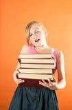 Młoda dziewczyna ono zmaga się trzymać stos książki Zdjęcie Royalty Free