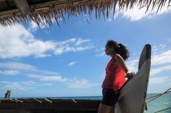 Młoda dziewczyna opiera na drewnianej łodzi zdjęcia royalty free