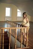 Młoda dziewczyna opierająca się na rzeźbiącym drewnianym poręczu Obrazy Royalty Free