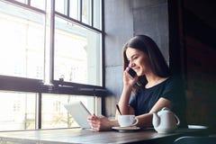 Młoda dziewczyna opowiada na telefonie komórkowym w sklep z kawą fotografia royalty free