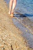 Młoda dziewczyna opuszcza ślada na piasku, chodzi wzdłuż seashore przy zmierzchem obraz stock