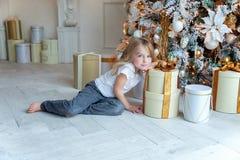 Młoda dziewczyna otwiera prezent pod choinką zdjęcie stock