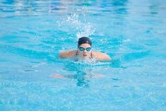 Młoda dziewczyna pływa motyliego uderzenia styl Zdjęcie Stock