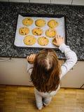 Młoda dziewczyna patrzeje świeżo piec ciastka zdjęcie royalty free