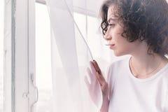 Młoda dziewczyna patrzeje okno w ranku Pojęcie zadumana samotność obrazy stock