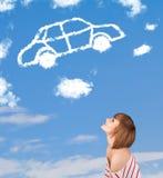 Młoda dziewczyna patrzeje samochód chmurę na niebieskim niebie Obrazy Royalty Free