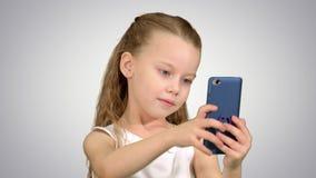 Młoda dziewczyna patrzeje w kamerę ono uśmiecha się brać selfie na białym tle Zdjęcia Royalty Free