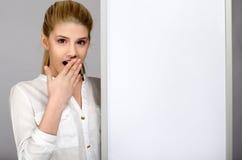 Młoda dziewczyna patrzeje zdziwioną pozycję blisko białej deski. Zdjęcia Royalty Free