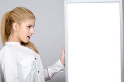 Młoda dziewczyna patrzeje zdziwioną pozycję blisko białej deski. Zdjęcia Stock