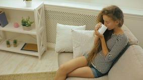 Młoda dziewczyna pije świeżego dojnego obsiadanie na kanapie zbiory