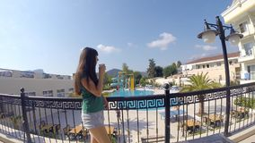 Młoda dziewczyna pije filiżankę kawy na hotelowym balkonie podczas wakacje Kobiety zamyślenie przyglądający nad hotelem out zbiory