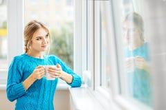 Młoda dziewczyna pije herbaty i patrzeje out okno przeciw jako tła popasu pojęcia dolarom szarość wiesza haczyka Zdjęcie Royalty Free