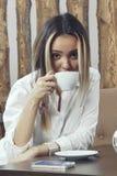 Młoda dziewczyna pije kawę od białej filiżanki przy stołem w kawiarni na którym kłama telefon Zdjęcie Stock
