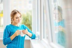 Młoda dziewczyna pije kawę z mlekiem i odbija Pojęcie Zdjęcia Royalty Free