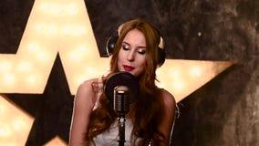 Młoda dziewczyna piosenkarz nagrywa piosenkę w muzycznym studiu zbiory wideo