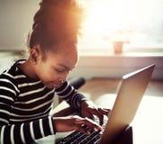 Młoda dziewczyna pisać na maszynie na laptopie Obrazy Stock