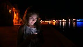 Młoda dziewczyna pisze w gonu na telefonie komórkowym na tła nocnym niebie zbiory