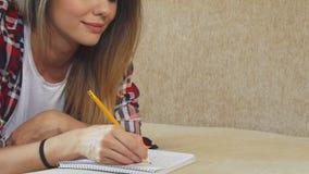 Młoda dziewczyna pisze w jej notatniku zbiory