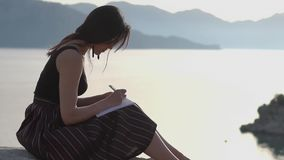 Młoda dziewczyna pisze w notatniku, siedząc na wybrzeżu w zwolnionym tempie zbiory wideo