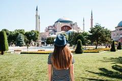 Młoda dziewczyna podróżnik w kapeluszu od plecy w Sultanahmet kwadracie obok sławnego Aya Sofia meczetu w Istanbuł Zdjęcia Royalty Free