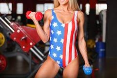Młoda dziewczyna pompowi bicepsy z barwiącymi dumbbells Wśrodku gym obrazy royalty free
