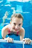Młoda dziewczyna pozuje w basenie trzyma krawędź - zdrowy styl życia zdjęcia stock