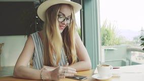 Młoda dziewczyna pracuje na smartphone w kawiarni Kobieta używa telefon komórkowego i ono uśmiecha się Żeński twórca zdjęcie wideo