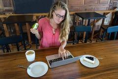 Młoda dziewczyna pracuje przy komputerem i tort, jedzenie przy komputerem, zły przyzwyczajenie je Fotografia Stock