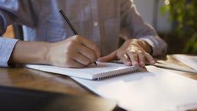Młoda dziewczyna pracuje z dokumentami i laptopem w nowożytnym biurze Kobiety ` s ręka pisze puszku na białym pustym notatniku da zdjęcie wideo