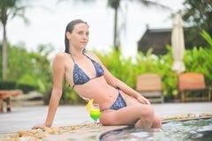 Młoda dziewczyna przy pływackim basenem pije koktajl Obraz Stock