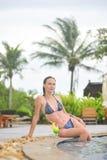 Młoda dziewczyna przy pływackim basenem pije koktajl Zdjęcie Royalty Free