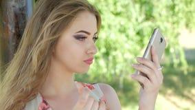 Młoda dziewczyna przystosowywa jej makeup z telefonem zdjęcie wideo