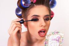 Młoda dziewczyna robi makeup i fryzura używać curlers obrazy stock
