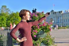 Młoda dziewczyna robi selfie od kwiatów łóżek na backgrou Zdjęcie Royalty Free