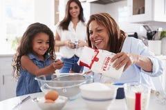 Młoda dziewczyna robi tortowi w kuchni z jej babcią, mum stoi dopatrywanie, selekcyjna ostrość zdjęcie stock
