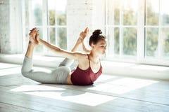 Młoda dziewczyna rozciąga jej kręgosłup w joga posturze obrazy royalty free