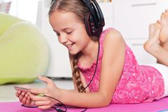 Młoda dziewczyna słucha muzyka na jej smartphone - kłamający na f Fotografia Stock