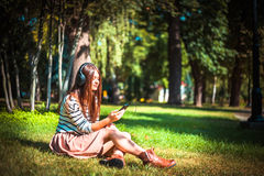 Młoda dziewczyna słucha muzyka w parku Obraz Royalty Free