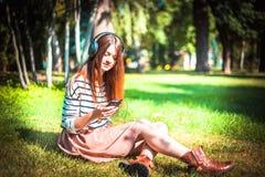 Młoda dziewczyna słucha muzyka w parku Zdjęcia Royalty Free