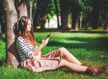 Młoda dziewczyna słucha muzyka w parku Obrazy Royalty Free