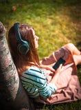 Młoda dziewczyna słucha muzyka w parku Zdjęcie Stock
