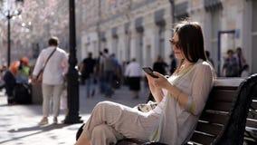 Młoda dziewczyna siedzi na ławce w ulicie na tle piękna biżuteria i druki, piszą wiadomości na twój zbiory