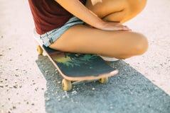 Młoda dziewczyna siedzi na deskorolka, tatuaż na jej nodze fotografia royalty free