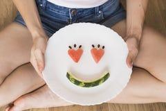 Młoda dziewczyna siedzi na drewnianej podłodze z białym talerzem w ona ręki Uśmiechać się twarze na białym talerzu obrazy royalty free