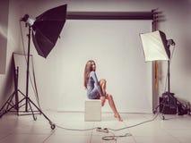 Młoda dziewczyna siedzi na sześcianie Stawia jej ręki na jej nagich kolanach W jeden szarym pulowerze Photoshoot w fotografii stu Obrazy Royalty Free