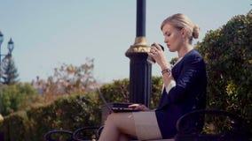 Młoda dziewczyna siedzi na ulicie obok działania za laptopem i budynku biurowego Laptop jest na jej podołku zdjęcie wideo