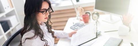 Młoda dziewczyna siedzi przy biurowego biurka i czeków dokumentami zdjęcie royalty free