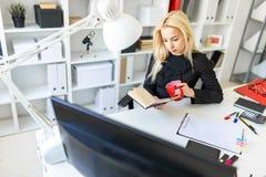 Młoda dziewczyna siedzi przy stołem w biurze, trzymający czytanie i filiżankę książka Obrazy Stock