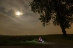 Młoda dziewczyna siedzi samotnie w zmroku Obrazy Royalty Free