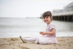 Młoda dziewczyna siedział na plaży z uśmiechem na jej twarzy fotografia stock